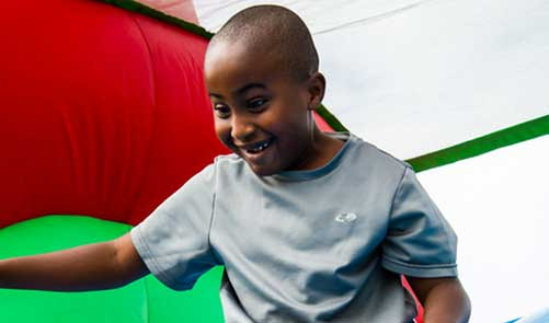 Boy smiling sliding down bounce house